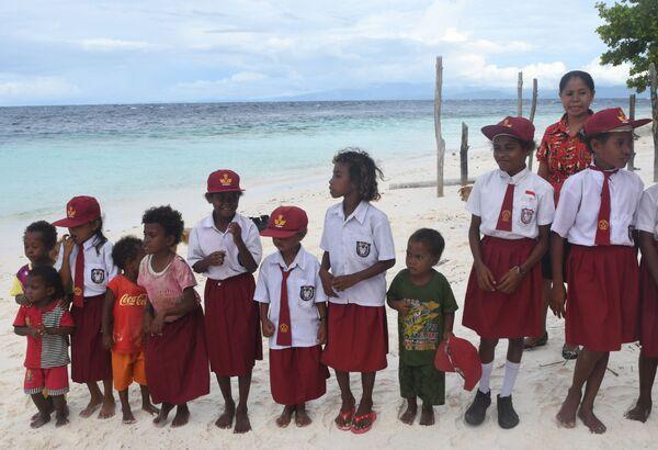 Los uniformes escolares son obligatorios en Indonesia, pero los estilos y colores pueden variar de una escuela a otra. Los estudiantes más jóvenes suelen llevar camisas blancas y pantalones cortos granates para los chicos, o faldas para las chicas. - Sputnik Mundo