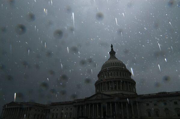 Los fuertes vientos también derribaron torres de alta tensión y  árboles, y provocó la explosión de varios transformadores.En la foto: la lluvia torrencial en Washington DC. - Sputnik Mundo