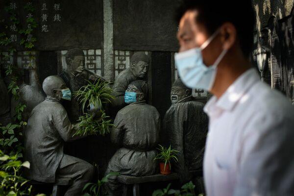 Un hombre pasa cerca de una escultura cubierta con mascarillas en el exterior de un restaurante en un callejón en Pekín, el 29 de agosto de 2021. - Sputnik Mundo