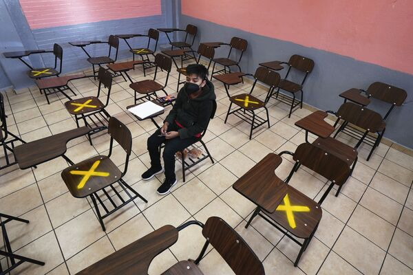 Un solo estudiante asiste a una clase presencial en una escuela secundaria de la República Argentina en el distrito de Iztacalco, Ciudad de México, el 30 de agosto de 2021, cuando comenzaron los estudios escolares para millones de niños mexicanos. Pero mientras unos de ellos van al colegio, los otros continúan estudiando desde casa debido a la pandemia. - Sputnik Mundo