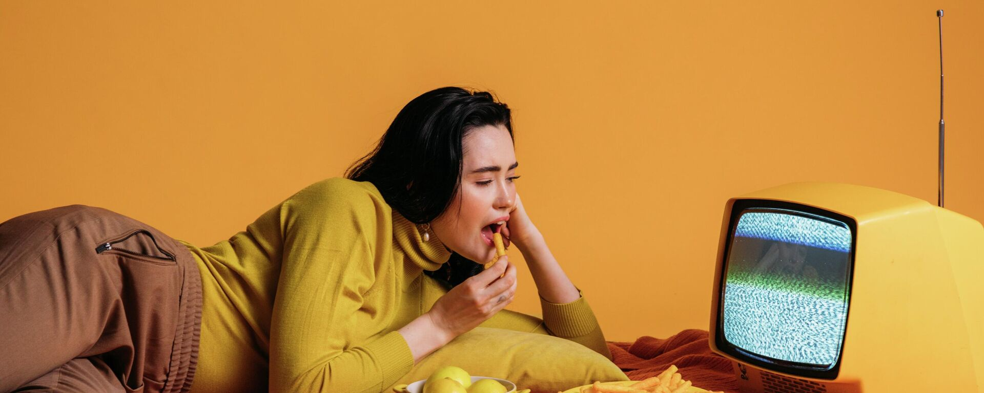 Una joven comiendo frente al televisor, imagen referencial - Sputnik Mundo, 1920, 03.09.2021
