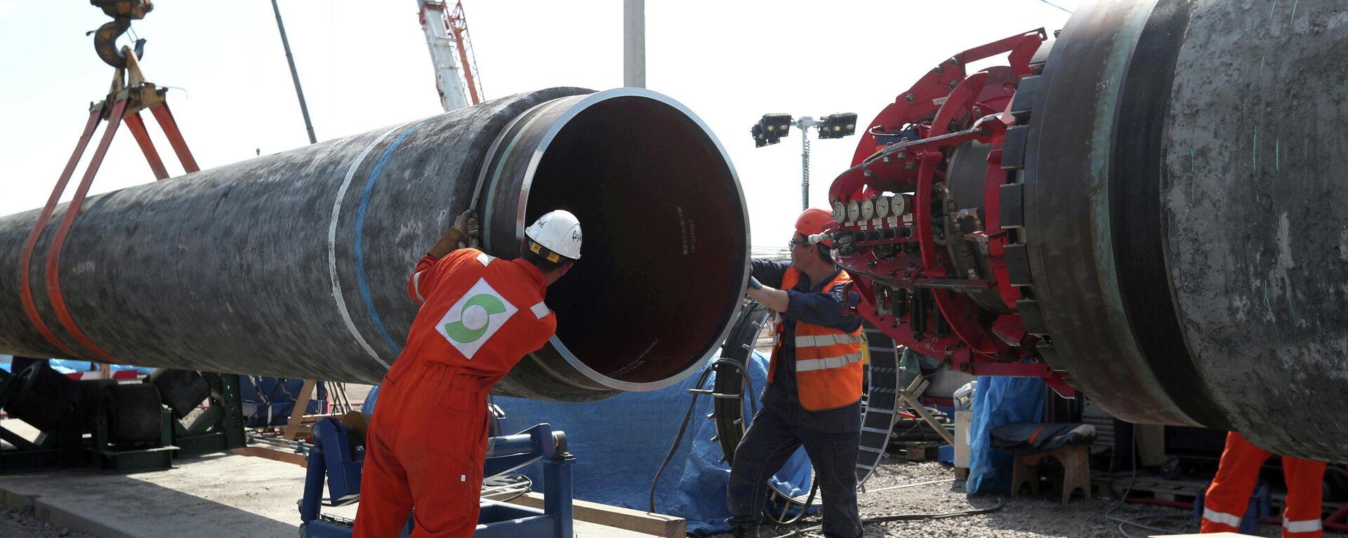 Unos trabajadores actúan en la construcción del gasoducto Nord Stream 2 - Sputnik Mundo, 1920, 07.09.2021