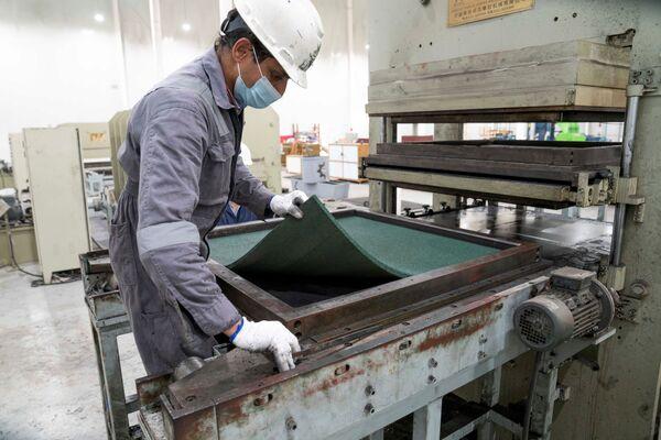 Allí ya han comenzado a procesarlos para fabricar suelos.En la foto: un trabajador de la planta de Salmi revisa un suelo de goma fabricado a partir de neumáticos reciclados.  - Sputnik Mundo