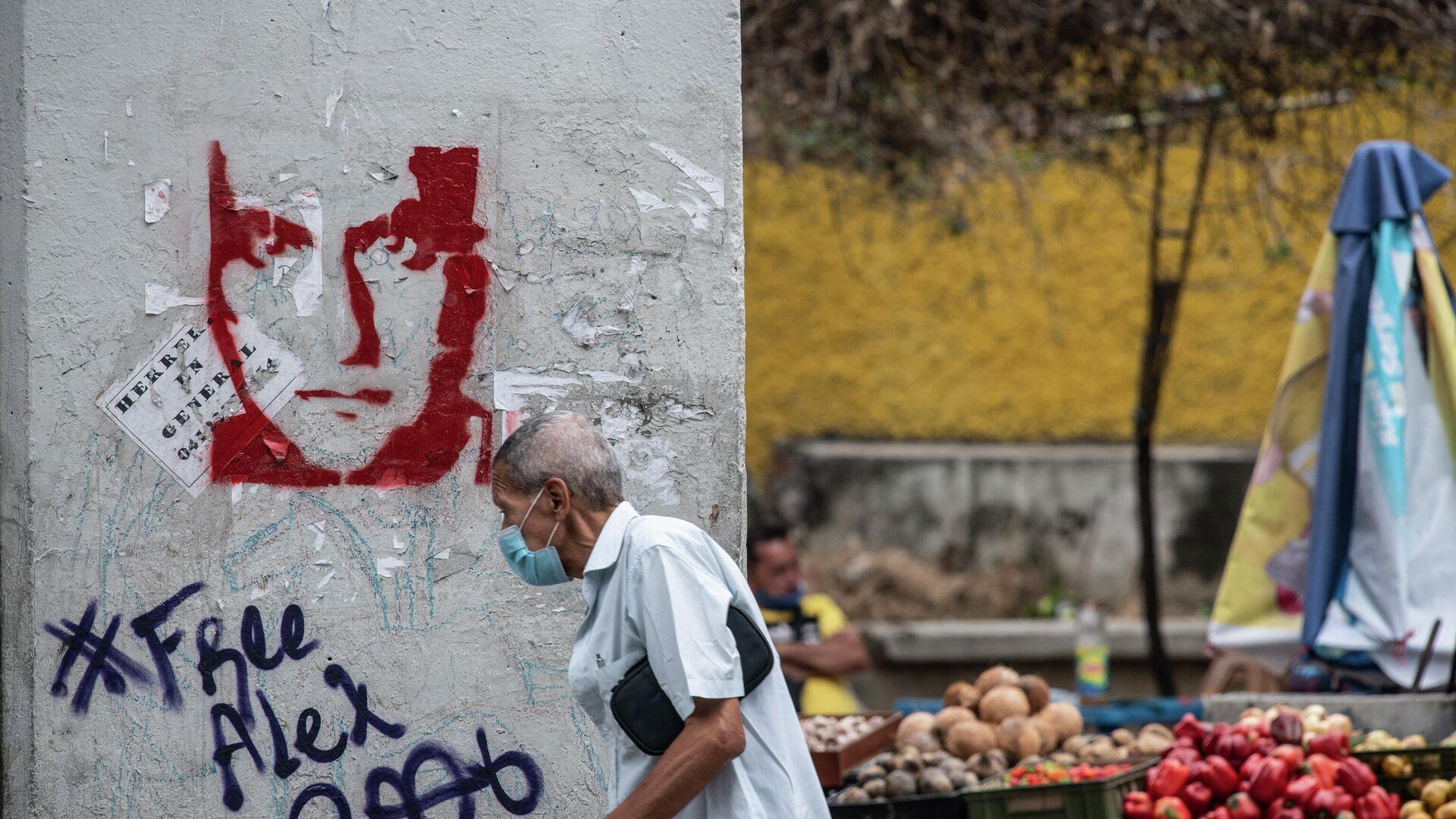 Un hombre camina frente a un graffitti con el rosto de Alex Saab en Caracas, Venezuela - Sputnik Mundo, 1920, 09.09.2021