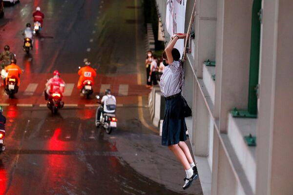 Una manifestante finge ahorcarse en una acción de protesta contra las medidas pandémicas en Tailandia. - Sputnik Mundo