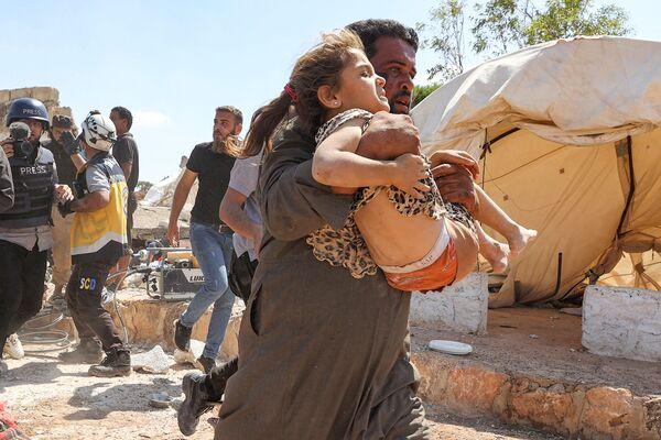 Un vecino de Idlib sostiene a una niña durante un ataque aéreo sobre un campo de refugiados ubicado a las afueras de la localidad siria de Kafraya. - Sputnik Mundo