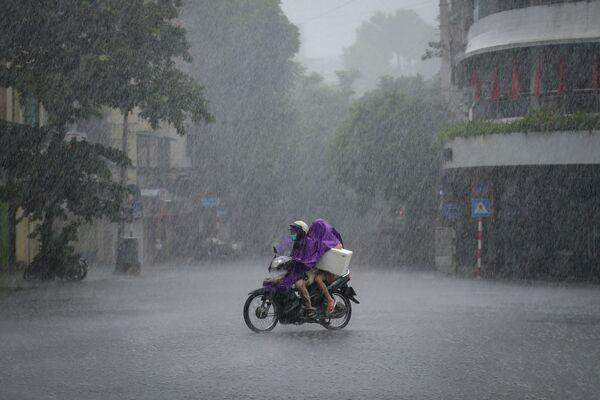 Un motociclista durante las fuertes lluvias en Hanoi, Vietnam. - Sputnik Mundo
