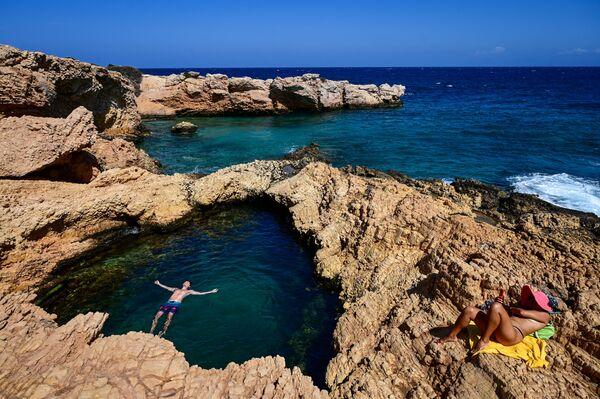 Unos turistas disfrutan del mar en la isla de Koufonissi, en el mar Egeo. - Sputnik Mundo