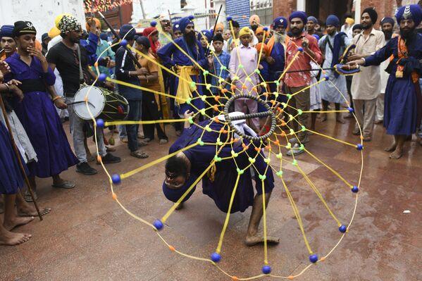 Un sij muestra un truco de arte marcial tradicional Gatka en el Templo Dorado de Amritsar, en la India. - Sputnik Mundo