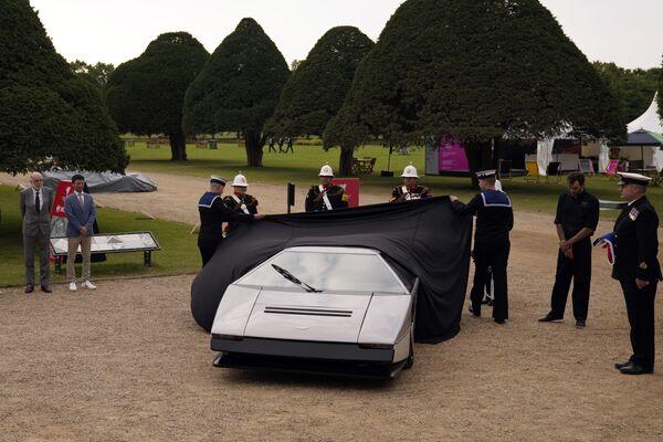 El trabajo de restauración duró 18 meses.En la foto: dos cadetas de la Armada Real del Reino Unido quitan el velo del Aston Martin Bulldog, mostrando al público el auto que fue restaurado tras estar en el olvido durante 35 años. - Sputnik Mundo