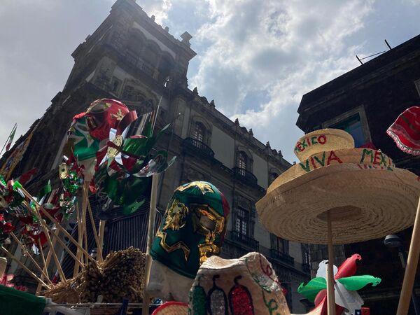 Además de escarapelas y banderas, los comerciantes ofrecen sombreros, máscaras y vestimenta típica. - Sputnik Mundo