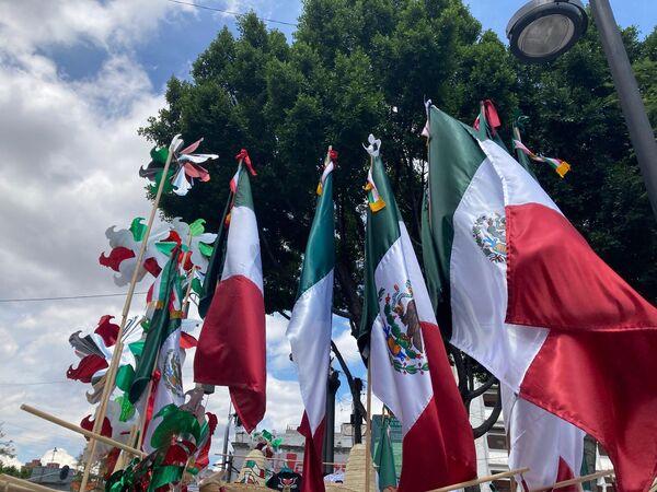 El emblema tricolor caracteriza la oferta de decena de puestos ambulantes en el centro de la capital mexicana. - Sputnik Mundo