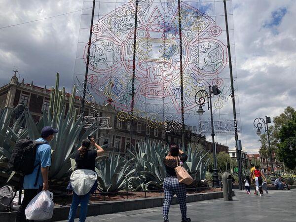 Los decorados se extienden hasta el costado izquierdo de la Catedral metropolitana, dónde se reproduce con luces la forma central de la piedra del sol, hallada enterrada bajo el Zócalo capitalino. - Sputnik Mundo