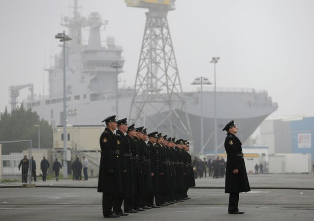 Russian sailors stand in formation in front of the Mistral-class helicopter carrier Vladivostok at the STX Les Chantiers de l'Atlantique shipyard site in Saint-Nazaire