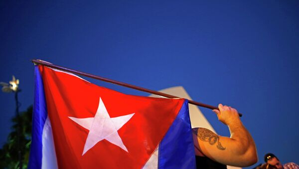 An anti-Castro Cuban exile holds a Cuban flag during a protest after the announcement of restoring diplomatic ties between Cuba and United States, at an area knows as 'Little Havana' in downtown Miami, Florida December 17, 2014. - Sputnik Mundo