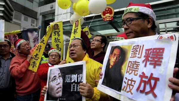 Manifestantes con los carteles del premio Nobel de la Paz Liu Xiaobo y a su mujer Liu Xia - Sputnik Mundo