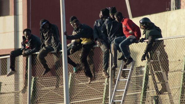 African migrants sit at the top of a border fence, as a Spanish Civil Guard tries to convince them to descend the stairs, during an attempt to cross into Spanish territories, between Morocco and Spain's north African enclave of Melilla December 30, 2014. - Sputnik Mundo