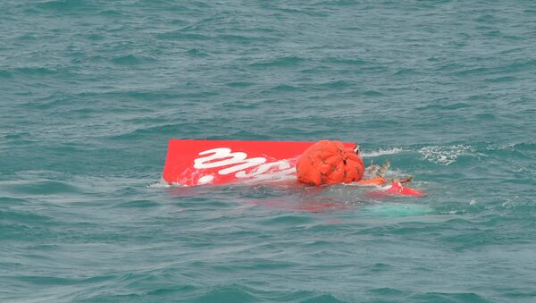 Part of the tail of AirAsia QZ8501 floats on the surface after being lifted as Indonesian navy divers conduct search operations for the black box flight recorders and passengers and crew of the aircraft, in the Java Sea January 10, 2015. - Sputnik Mundo