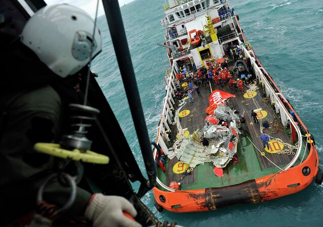 The tail of AirAsia QZ8501 passenger plane is seen on the deck of the rescue ship Crest Onyx from an Indonesian Super Puma military helicopter after it was lifted from the sea bed, south of Pangkalan Bun, Central Kalimantan