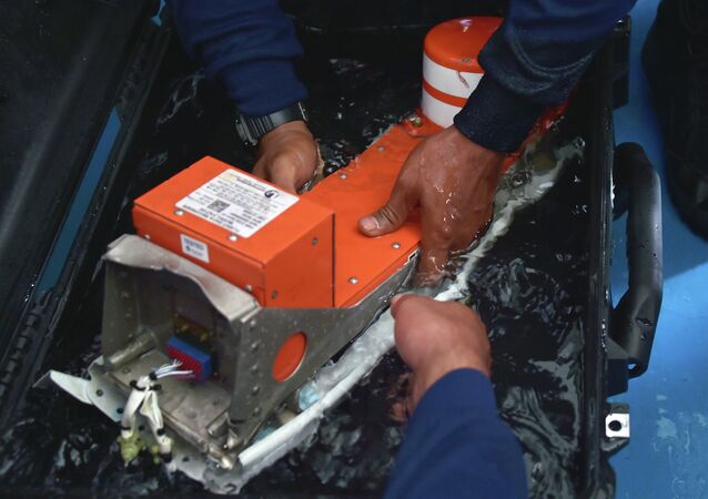Indonesian divers onboard the Indonesian navy vessel KRI Banda Aceh handle the FDR (Flight Data Recorder) of the AirAsia flight QZ8501 after it was retrieved from the Java Sea on January 12, 2015