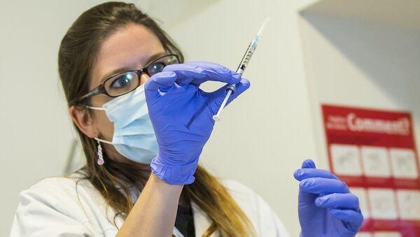 A nurse holds a dose of experimental vaccine cAd3-EBOZ Lau - Sputnik Mundo