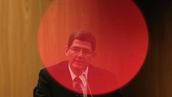 Brazil's Finance Minister Joaquim Levy, pictured through a red LED light of a camera, reacts during a news conference at Brazil's Central Bank in Brasilia January 5, 2015. - Sputnik Mundo