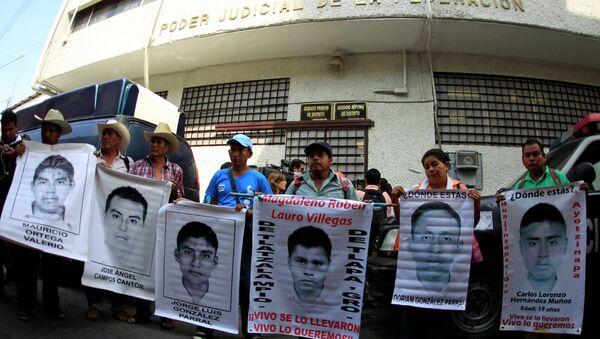 Familiares sostienen carteles de los 43 estudiantes desaparesidos - Sputnik Mundo