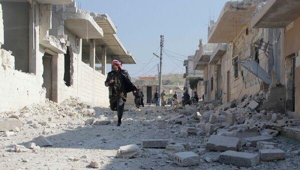 A man runs towards a site damaged by what activists said was shelling from forces loyal to Syria's president Bashar Al-Assad on Al-Beera village East Khan Sheikoun, Idlib countryside January 24, 2015. - Sputnik Mundo