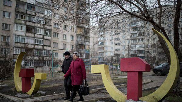Local residents walk past Soviet-era hammer and sickle sculptures outside an apartment building damaged after Saturday's shellingin Mariupol, Ukraine - Sputnik Mundo