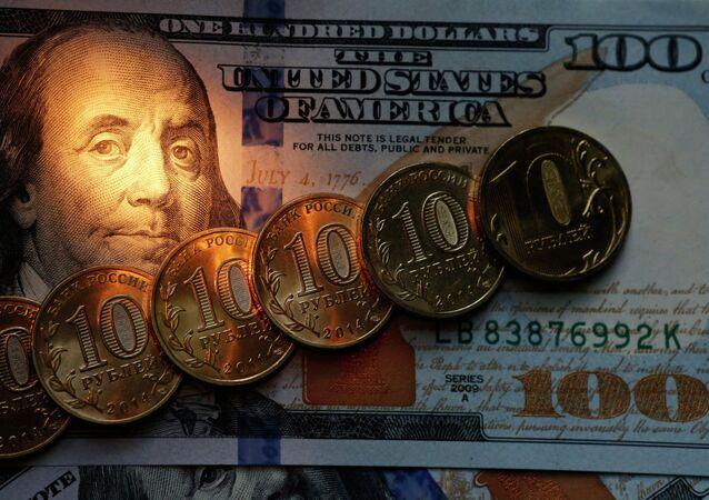 Monedas del rublo y cien dólares de EEUU