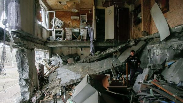 A man stands in a flat at a residential block damaged by a recent shelling in Yenakieve town, northeast from Donetsk, February 2, 2015 - Sputnik Mundo