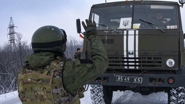 A Donetsk militia signals for a Ukrainian convoy truck to stop on the road near the Airport of Donetsk - Sputnik Mundo