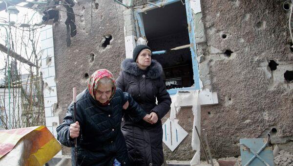 People walk outside a house damaged by shelling in Donetsk - Sputnik Mundo