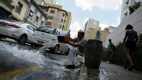 A man pours excess water on to the road after filling up his barrel in Sao Paulo February 3, 2015 - Sputnik Mundo