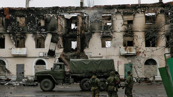 Members of the armed forces of the separatist self-proclaimed Donetsk People's Republic gather near a building destroyed during battles with the Ukrainian armed forces in Vuhlehirsk, Donetsk region, February 4, 2015 - Sputnik Mundo