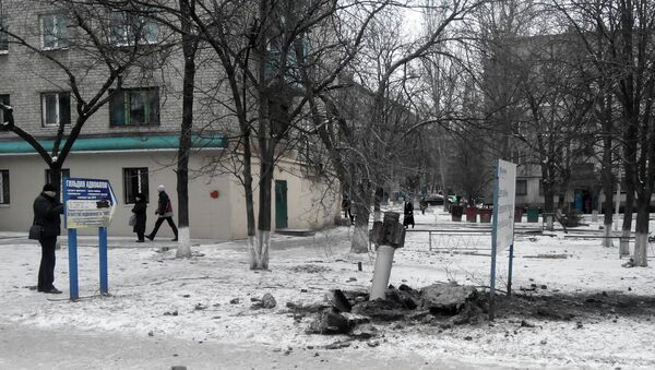 A resident passes by an unexploded rocket in a living area in Kramatorsk, Ukraine, Tuesday, Feb.10, 2015 - Sputnik Mundo