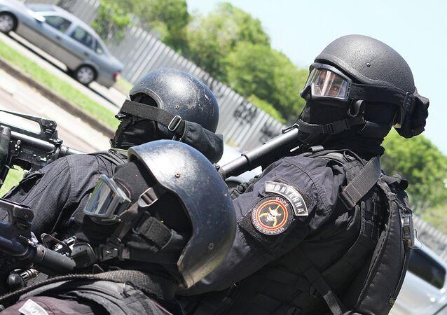 Agentes de la Unidad Táctica del BOPE aguardan la orden de asalto a las afueras de la estación Golfe Olímpico durante el simulacro de secuestro