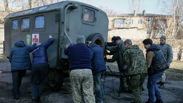Members from a First Volunteer mobile hospital push a medical trailer in Artemivsk - Sputnik Mundo