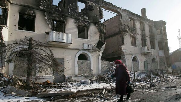 A woman walks past a damaged building in the town of Vuhlehirsk near Donetsk, Ukraine, February 14, 2015. - Sputnik Mundo