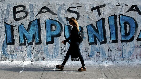 A woman walks in front of graffiti that reads Enough of impunity that was painted before a demonstration outside Argentina's Congress in Buenos Aires February 4, 2015 - Sputnik Mundo