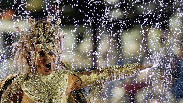 Rain water splashes up onto a performer on the float of the Viradouro samba school, during the Carnival parade at the Sambadrome in Rio de Janeiro, Brazil, Sunday, Feb. 15, 2015 - Sputnik Mundo