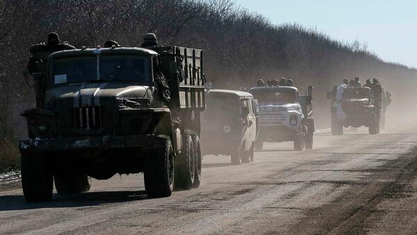 Ukrainian servicemen ride on military vehicles as they leave an area around Debaltseve, eastern Ukraine near Artemivsk, February 18, 2015. - Sputnik Mundo