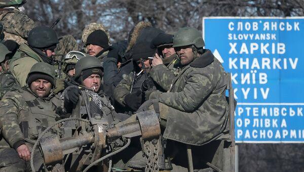 Ukrainian servicemen ride on a military vehicle as they leave the area around Debaltseve, February 18, 2015 - Sputnik Mundo