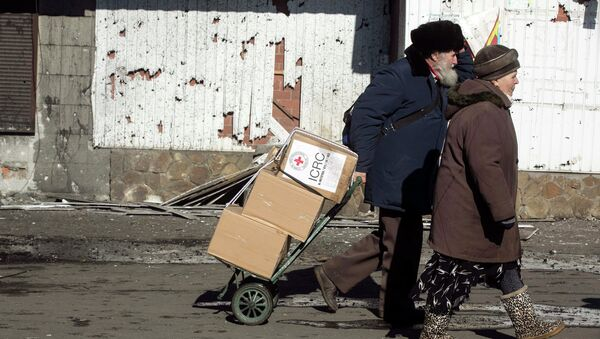 A man walking with a woman pulls a trolley with International Committee of the Red Cross relief packages in the town of Debaltseve February 22, 2015 - Sputnik Mundo