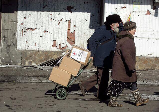Hombre y mujer con paquetes de la Cruz Roja