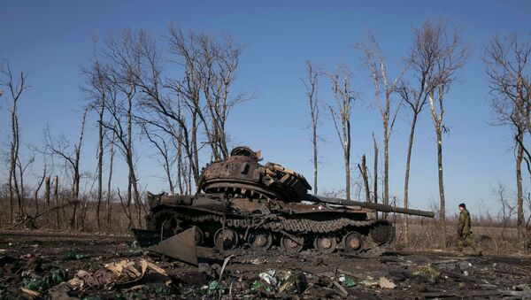 A fighter with the separatist self-proclaimed Donetsk People's Republic army looks at a destroyed Ukrainian army tank near the town of Debaltseve February 22, 2015 - Sputnik Mundo