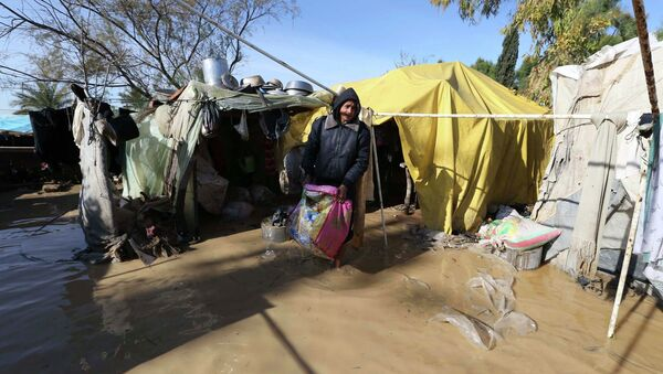 Palestinian man salvages his belongings from his dwelling after it was flooded by rain water - Sputnik Mundo