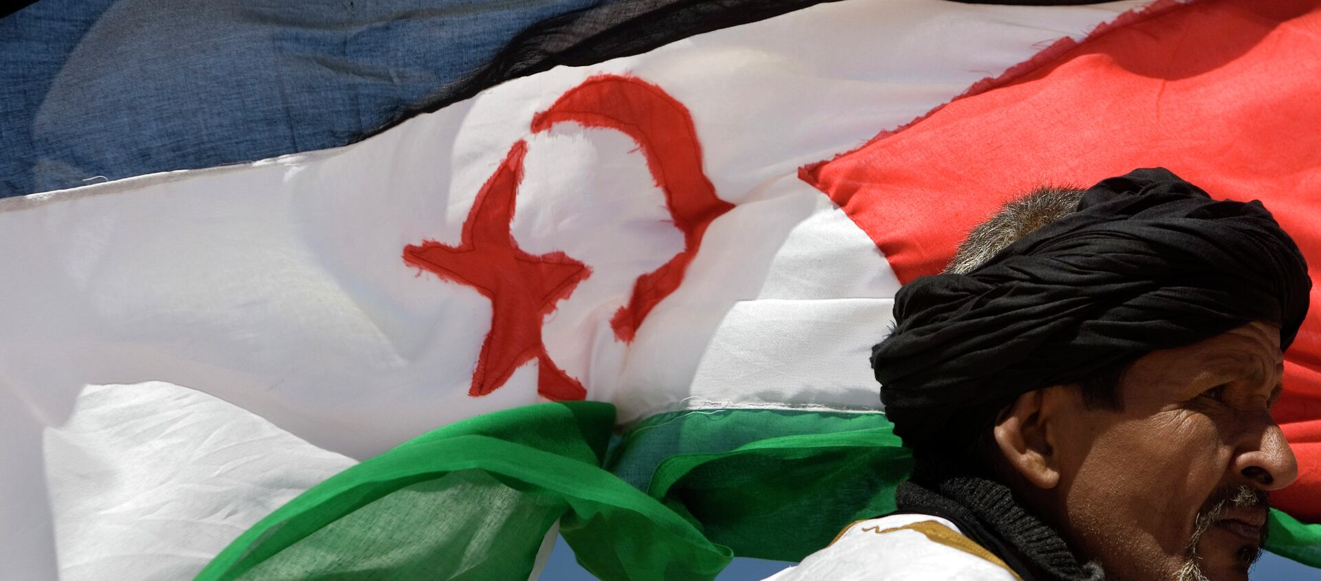 A pro-independence Polisario Front supporter looks on during a military parade as a Western Sahara flag flies in the breeze in the village of Tifariti - Sputnik Mundo, 1920, 13.12.2020
