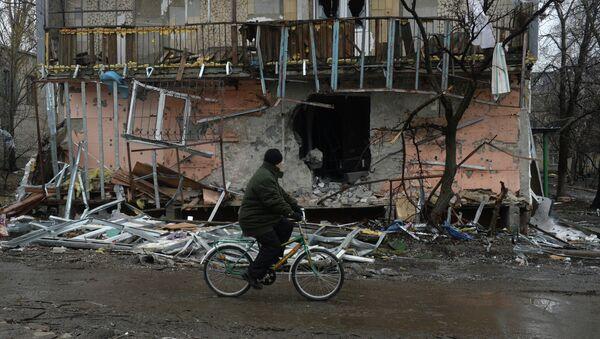 Житель города Дебальцево едет на велосипеде мимо разрушенного в результате обстрелов во время боевых действий жилого дома. - Sputnik Mundo