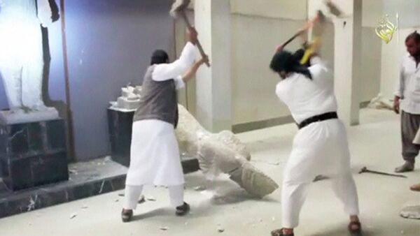 Men use sledgehammers on a toppled statue in a museum at a location said to be Mosul - Sputnik Mundo
